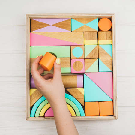 A box of children's wooden designer in his hands. Wooden constructor for children. Colorful toys made of natural materials. Zero waste.