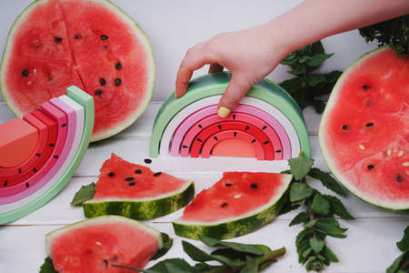 Wooden watermelon. Children's wooden toys. Toy rainbow made of natural wood for a small child. Hand holding a wooden rainbow in the form of a watermelon. Zero waste.