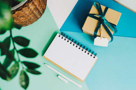 A gift box, a room flower, a notebook for records and a pen lie on a light background. Abstract background of blue, white and green.