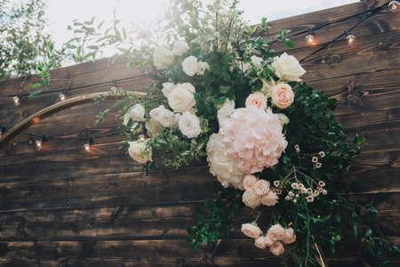 Beautiful wooden arch for a wedding ceremony. Wedding ceremony in the fresh air. The arch is decorated with fresh flowers and greenery. Wedding decor. Fresh greenery, flowers adorn the wedding arch.