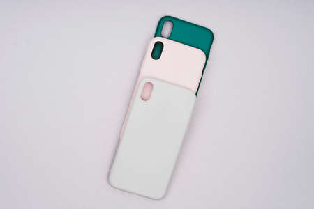 Three silicone cases for a smartphone. Covers of gray, green and powder color. A set of three covers of natural colors. Gray, green and pink smartphone cases.