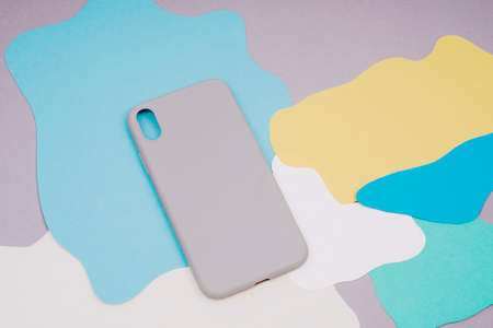 The gray silicone case for the smartphone lies on a multi-colored background. Protect your phone.