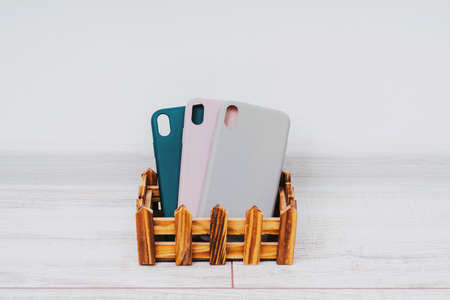 Three silicone cases for a smartphone stand in a wooden stand. Gray, green and pink smartphone cases. Protect your phone. 版權商用圖片