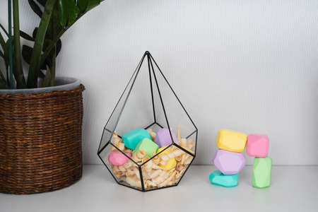 Children's wooden constructors in a glass florarium. Colored cubes of various shapes.