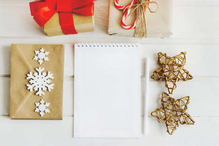 The notebook is open with a clean white page for recordings or sketches. New Years still life, view from above. Notebook, gift boxes, craft envelopes for letters, wooden snowflakes, decorative stars.
