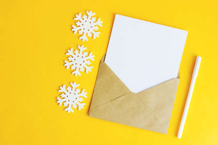 An envelope with a white letter sheet and wooden snowflakes on a yellow background. Christmas background for design and text. Snowflakes of different sizes. Selective focus.