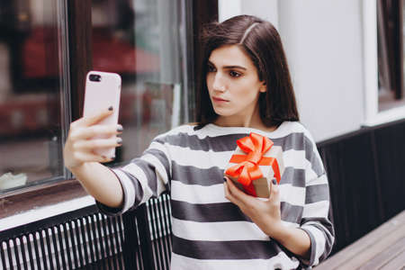 Gift from a beautiful girl in her hands. A girl in a striped jumper takes a selfie with a gift. A gift tied with a red satin ribbon. Gift for Christmas, birthday, Valentines day. 版權商用圖片