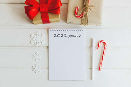 Christmas composition. Notepad with goals for 2021. Notepad, pen, gift boxes, letter envelopes, wooden snowflakes and stars. Christmas striped candy canes. Selective focus.