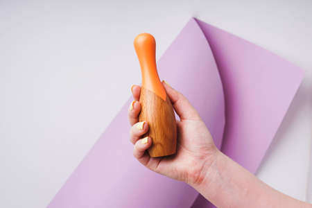 Wooden bowling pin. Pin in his hand. Childrens toy made of natural material.