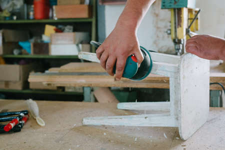 Restoration of furniture. Grinding machine.