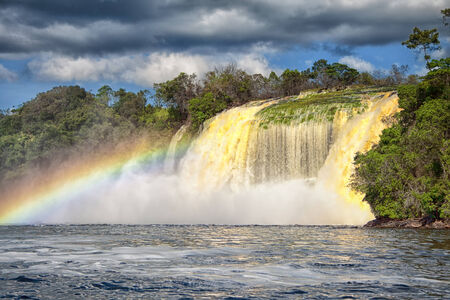 Gorgeous Waterfall and a Rainbow in the Midday Time in Canaima Stock Photo