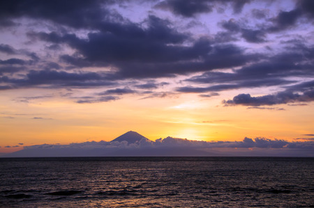 fata morgana: Volcano silhouette above clouds stripe between sea water and sky Stock Photo