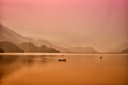 Fisherman boats at the lake surrounded by hills in the dim red light of a sunrice photo