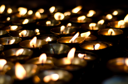 darkness: Lit candles in the darkness Stock Photo