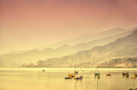 Fisherman boats at the lake surrounded by hills in a pinkish-yellow light of a sunrice photo