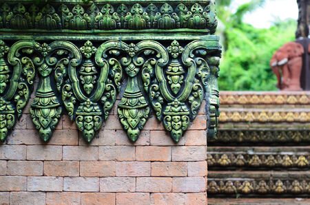 Closeup of a brick wall with traditional Balinese decorations photo