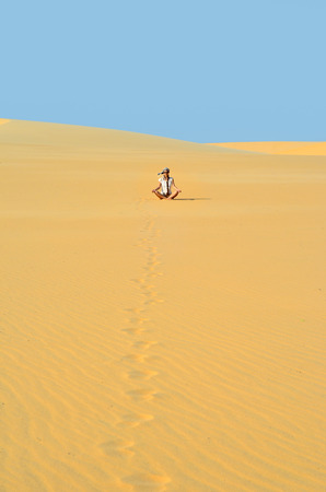 ander: Young girl meditating in golden sands of a desert ander bright blue sky of a hot summer day