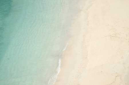 above water: Sea water meets white sand - aerial view to the beach