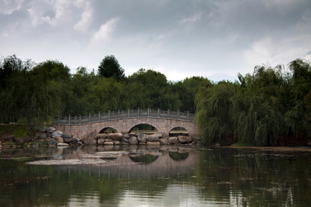 lost lake: Traditional Chinese stone bridge across the lake lost in green trees in a park