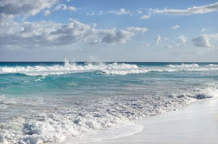White foamy waves and gradually darkening color of sea water with stripe of white sandy beach - perfect travel background