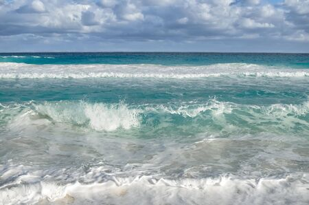 perfect waves: White foamy waves and gradually darkening color of sea water with stripe of white sandy beach - perfect travel background