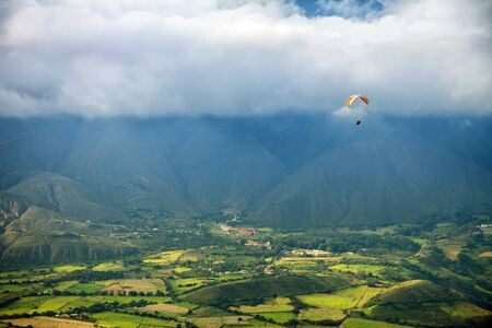 Paragliding in mountains above fields and villages - view from air Stock Photo