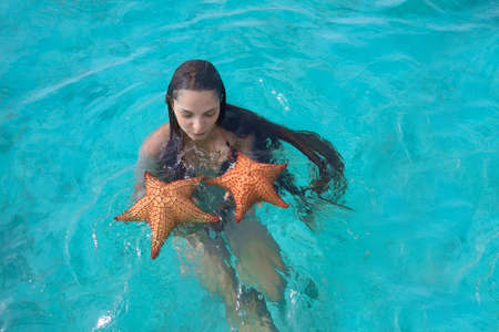 snorkle: Wet young woman with super long hair in turquoise sea water holding two big starfish in her hands