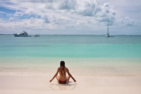 long hair: Back view of young woman with super long hair and in swimsuit sitting at white sand beach with turquoise sea water and few yachts at the horizon Stock Photo