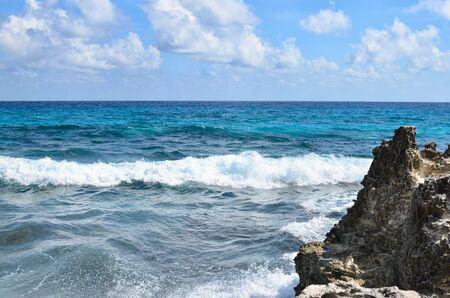 ocean waves: Blue ocean waves at rocky coast