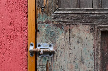 locked: Closeup of red wall and vintage door locked with latch Stock Photo
