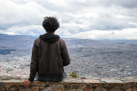 Anonymous guy with black curly hair sitting on stone wall overlooking Bogota city