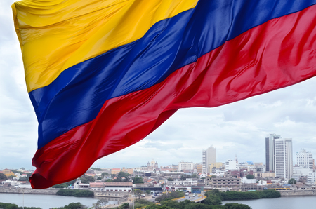 Colombian flag waving on the wind and modern Cartagena district behind it Foto de archivo