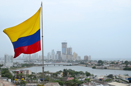 colombian flag: Colombian flag waving in the wind and Cartagena costal district behind it