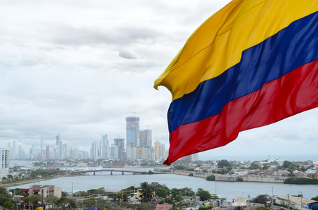 Colombian flag waving on the wind and modern Cartagena district behind it Reklamní fotografie