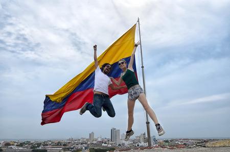 bandera de colombia: Feliz pareja de jóvenes saltando delante de la bandera colombiana con la ciudad de Cartagena en el fondo Foto de archivo