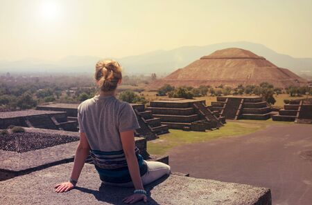Young woman sitting at the edge of ancient pyramid at Teotihuacan Stock Photo