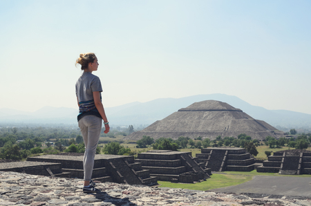 Young woman standing at the edge of ancient pyramid at Teotihuacan