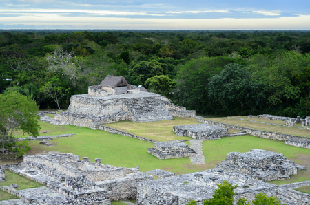 constraction: Aerial view to Mayan ruins and house on top of pyramid surrounded by jungle