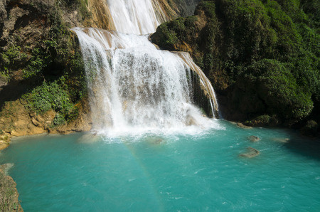 faint: View to amazing waterfall with turquoise pool surrounded by green rocks and a faint rainbow