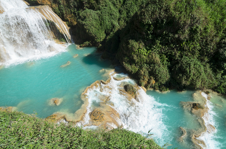 downstream: Downstream of a waterfall with turquoise pools and faint rainbow