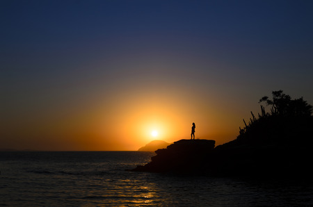 breakage: Silhouette of a woman standing at the breakage at the rosky beach at the sunset