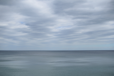 greyish: Pale cloudy sky over dim greyish sea water Stock Photo