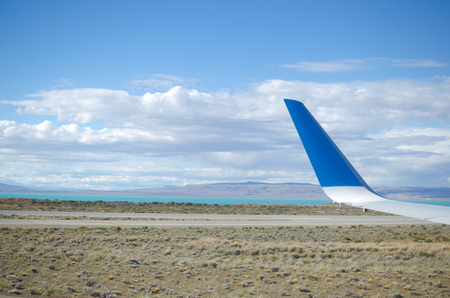 calafate: Airplane wing and view to landing strip, desert and lake
