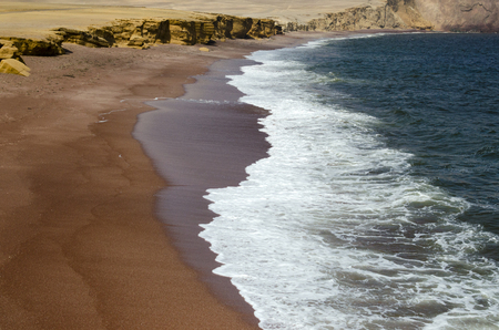 Red beach, yellow cliff and blue ocean Stock Photo