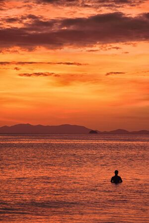 Man in the sea during stunning sunset