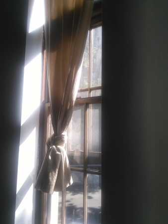 Morning light coming through window with beige curtain