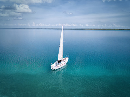 BACALAR, MEXICO, 07 OCTOBER 2017: White sailing boat in the lagoon - shot from drone