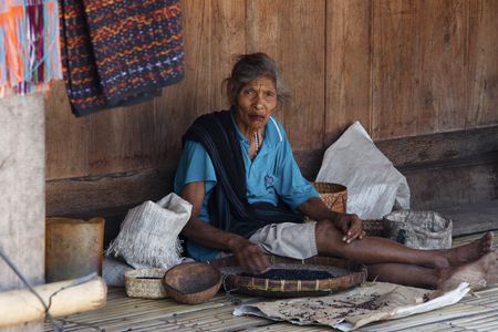 BENA, FLORES ISLAND, INDONESIA, 17 APRIL 2012: old indigenous woman sorts out beans on the porch of her rustic house 新聞圖片