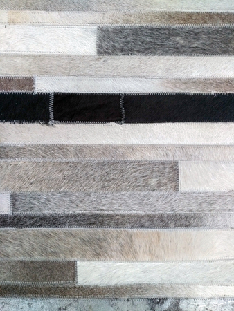 Background of carpet surface made of pieces of animal skins. White, black, grey and brownish patched stitched together, each has square form. Fancy carpet with zero love for animals.