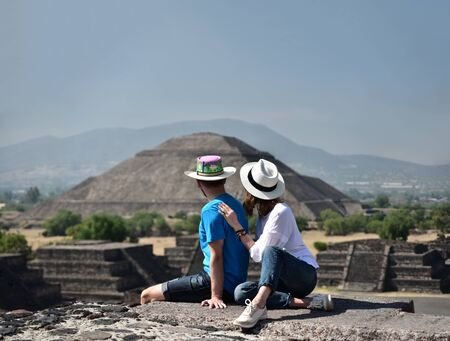 Couple sitting on Pyramid of the Moon and overlooking Pyramid of the Sun in Teotihuacan, Mexico. Anonymous back view of yound people travelling for there summer vacations. Travel destination for exploration of cultural and historical heritage.